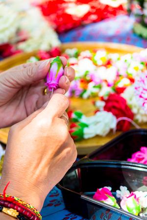 Thai woman making a tradition Thai flowers garland activities in Songkran festival, Bangkok Thailand.