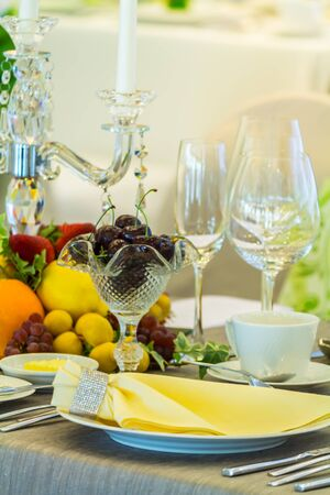 Party dinner table setting with tableware and silverware and glasses set and Candlestick and flower in restaurant.