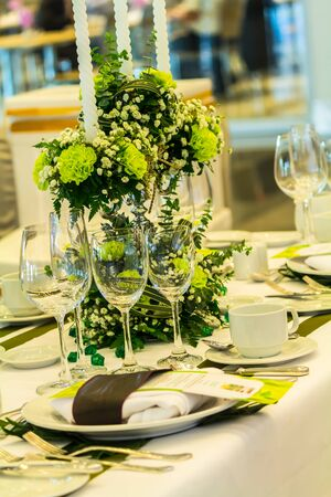 Party dinner table setting with tableware and silverware and glasses set and Candlestick and flower in restaurant. 스톡 콘텐츠