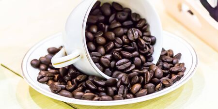 Raw roasted coffee beans in cup.