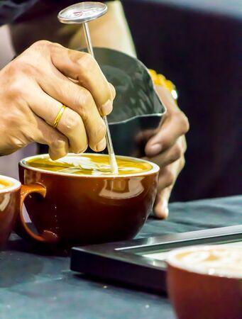 Showcase Barista making Latte art coffee and Barista pouring fresh milk create art pattern on Latte coffe.