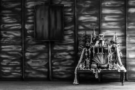black and white Halloween still life Thai theme: Scary decorated dark room with witch altar table covered in spider webs,skull, candlestick, devil doll and old wood wall background.
