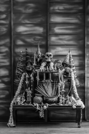 black and white Halloween still life Thai theme: Scary decorated dark room with witch altar table covered in spider webs,