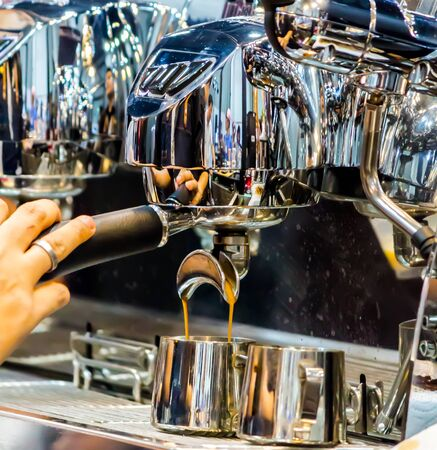 Showcase coffee maker by Espresso Machine pouring fresh coffee into cups at Local Coffee Shop.