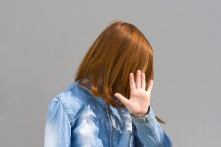 objecion: Chica esconde su cara  Foto de archivo