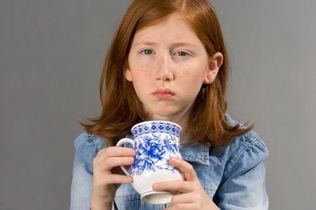 frowned: Girl drinking tea trying to awaken