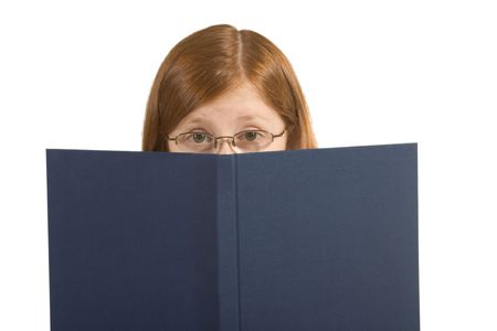 Read-haired Girl looking from behind the book photo