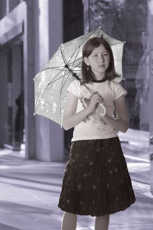 Girl with umbrella standing on the street photo
