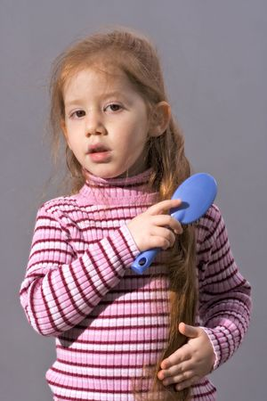 comb hair: Redheaded girl grooming her hair