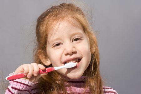 女の子彼女の歯ブラシで歯を磨く