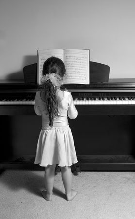 girl playing piano (BW), back view photo