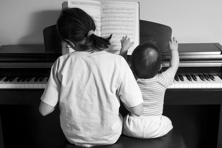 duet: children playing piano (BW), back view Stock Photo