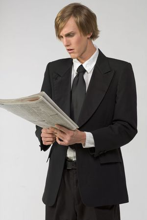 apparently: Businessman reading newspaper and apparently shocked by the content