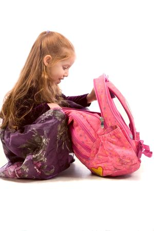 Very young schoolgirl looking into her pink backpack photo