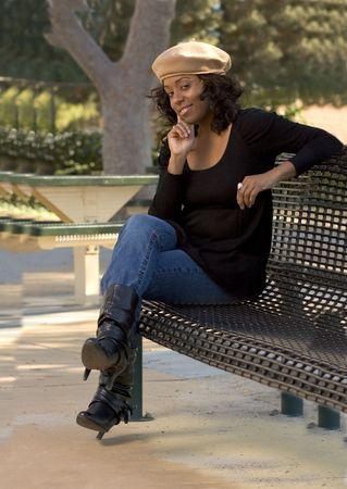 flirty: Portrait of Flirty African-American girl sitting on the bench Stock Photo