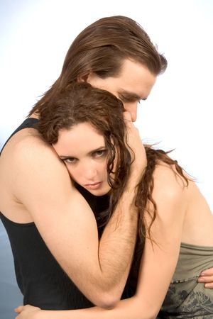 young man hugs and comforts young female in tears Stock Photo
