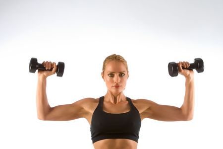 Blonde female working out with black dumbbells photo