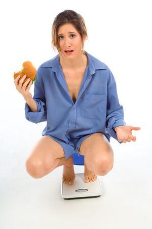 Female on weight scale eating hamburger Stock Photo - 963978