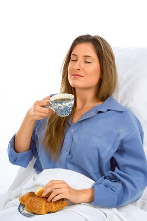 Female drinksÊ her coffee with croissant in the bed