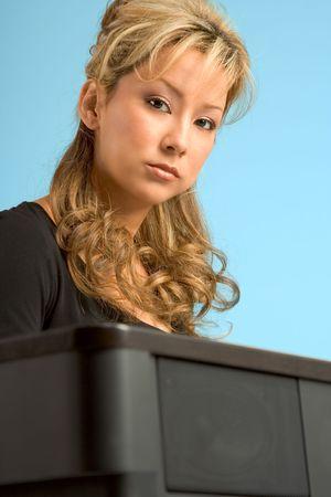 blonde hispanic: Blonde Hispanic Girl sitting by electronic piano Stock Photo
