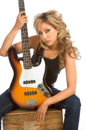 Portrait of Girl sitting on the box with bass guitar photo