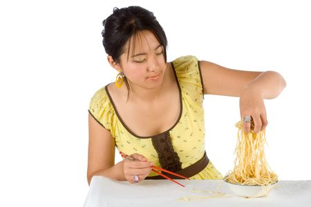 Chinese woman eating noodles with hands and chopsticks  photo