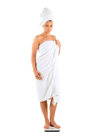 Beautiful Girl checking her weight wrapped in white bath towel