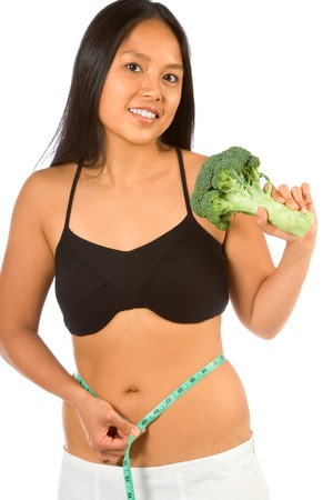 Asian woman holding broccoli and measuring her waist photo