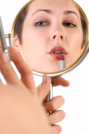 Girl uses lipstick (view through reflection in mirror) Stock Photo - 1448236