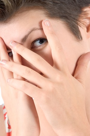 Young woman peeks through her fingers photo