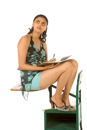 Female college student sitting on desk with notebook photo