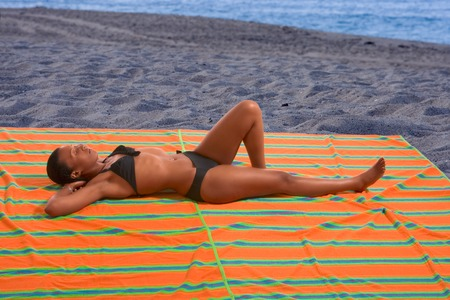 African-American female relaxing and taking sunbath by sea photo
