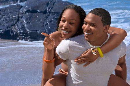 Attractive African-American young couple having fun on beach photo