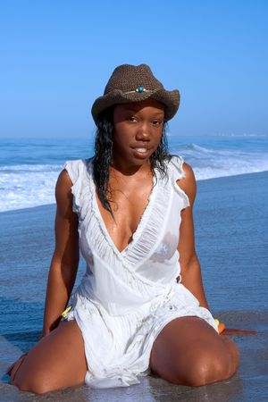 African-American woman in hat posing on beach photo