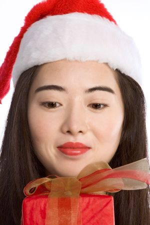 Asian girl in Santa hat looking on wrapped gift-box photo