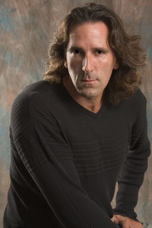 Studio portrait of mid aged man with long hair