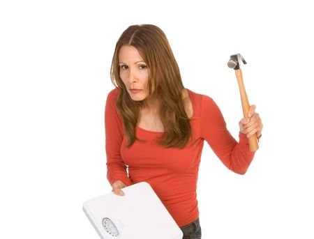underweight: Middle aged Woman hits weight scales by hammer Stock Photo