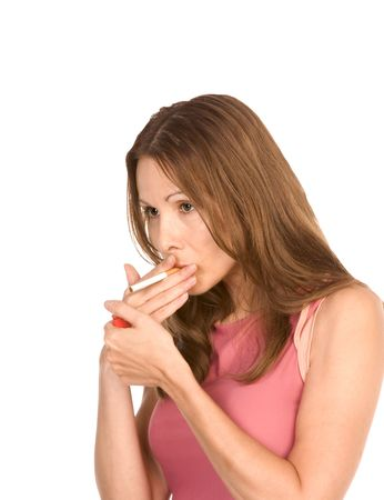 Middle-aged woman in pink top lights cigarette photo