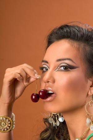 Young woman eating ripe red sweet cherries photo