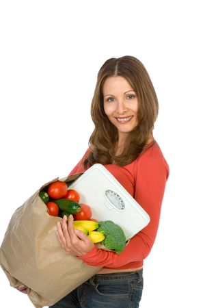 scandinavian descent: Middle aged woman holds back of vegetables and weight scales Stock Photo