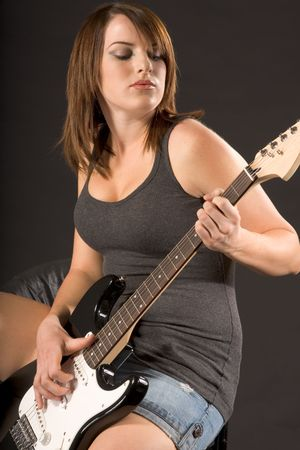 Joven mujer sentada y tocando guitarra el�ctrica  Foto de archivo - 2349375