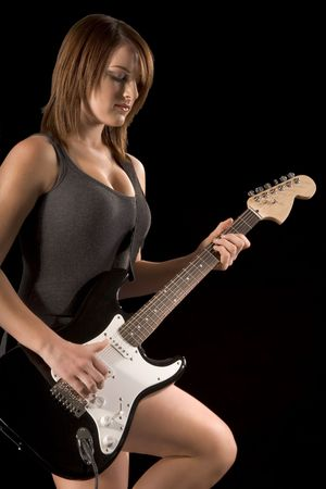 young Girl playing electric guitar in dark