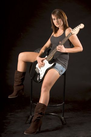 Teenaged girl sitting and playing electric guitar photo