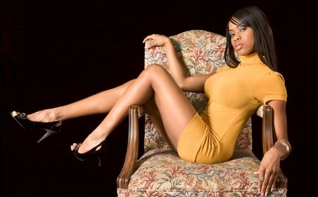 Glamorous African-American girl in yellow dress sitting with legs high in chair Stock Photo - 2490000