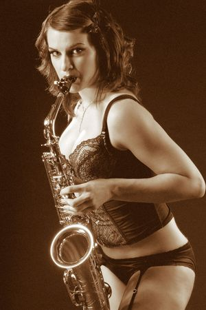 (Filtered version of picture #2349374) Woman with saxophone in retro lingerie. Image stylized as old picture including adding some artificial grain. Stock Photo - 2570723