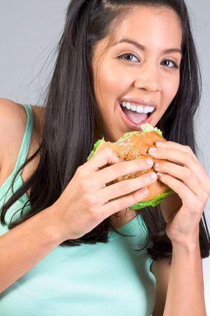 pause repas: Cheerful Latina fille de manger un hamburger au cours de pause d�jeuner  Banque d'images