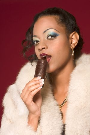 Portrait of young beautiful woman eating chocolate photo