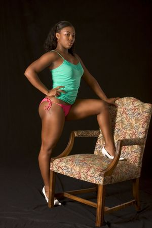 Sexy Glamorous black girl in lingerie sitting with one leg on chair photo