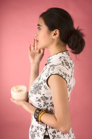 Chinese girl in white cheongsam applying cream on her face photo