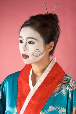 exoticism: Asian female with geisha style face paint in yukata (kimono) Stock Photo